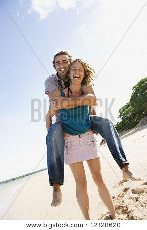 Mid-adult Caucasian woman giving man piggyback ride on beach.