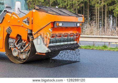 Road roller flattening new asphalt, industrial place