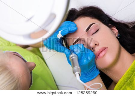 Top View Of Cosmetologist Applying Permanent Make Up On Eyebrows