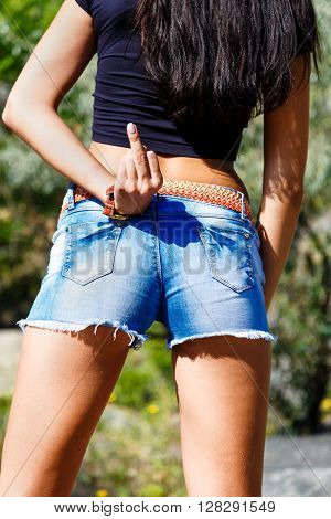 Sexy girl in jeans shorts with fit ass show middle finger up you off sign Outdoor funny lifestyle portrait concept of brutal rebel punk indecent