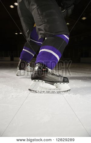 Low angle of hockey player's legs and skates on ice rink.
