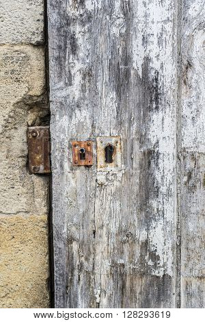 Weathered Wooden Door With White Paint Chipped And Peeling.