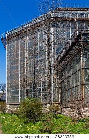 greenhouse in sankt-peterburg botanic garden. old architecture from glass and metal in clear sunny day poster