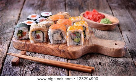 Homemade sushi with salmon, smoked eel, curd cheese and vegetables on a wooden background