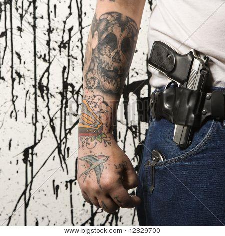 Caucasian tattooed man wearing holster with gun.