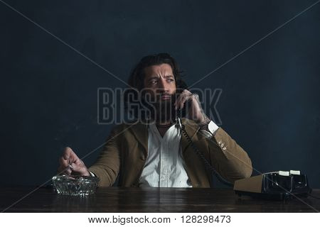 Retro 1970 Undercover Agent With Beard Calling Behind Desk While Smoking Cigarette.