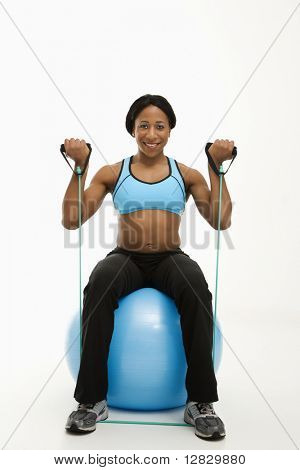 African American young adult woman sitting on exercise ball using resistance tube.