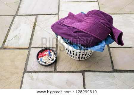 Full washing basket and pegs situated on a patio area