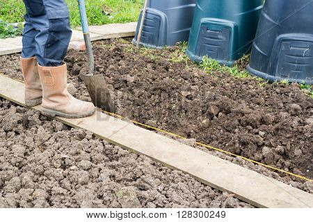 Gardener digging over an allotment and preparing soil