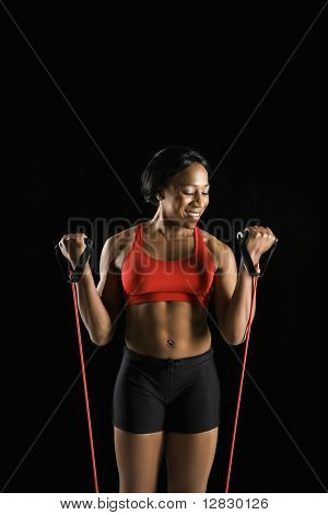 Smiling African American young adult woman exercising with resistance tube.