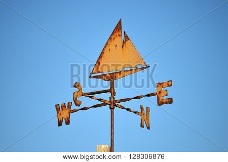 Rusty orange yacht weather vane on blue sky
