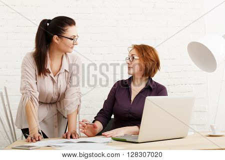 Two women in the office argue. Teamwork problem, business communication. Compare mobile version of site. Conflict, misunderstanding while discuss project. Start up discussion. Female coworkers.