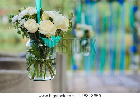 White roses and other flowers in glass jar hung in wedding party. White roses and chrysanthemum in vase  with water. Wedding arch, decorated with colored ribbons in background. Wedding decorations.