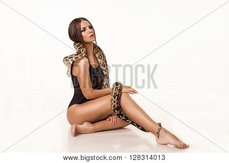 Youth women with perfect body and tan. The snake encircles the body. Isolated on white