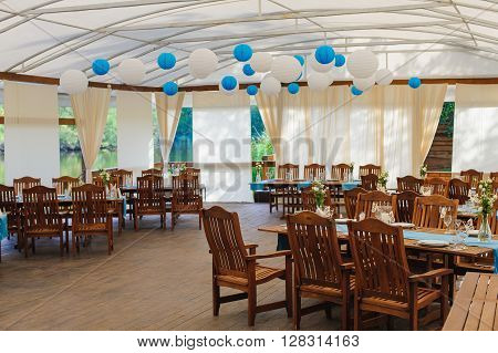 Wedding tent on the river bank. Wooden tables and chairs, wedding decor. Flowers in glass bottles. Paper lanterns. Rustic style.
