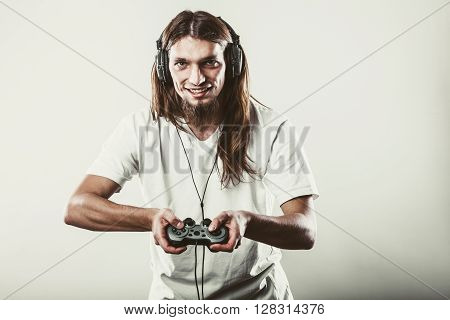 Playing games. Young smiling cheerful man play on console xbox playstation. Guy with pad joystick. poster