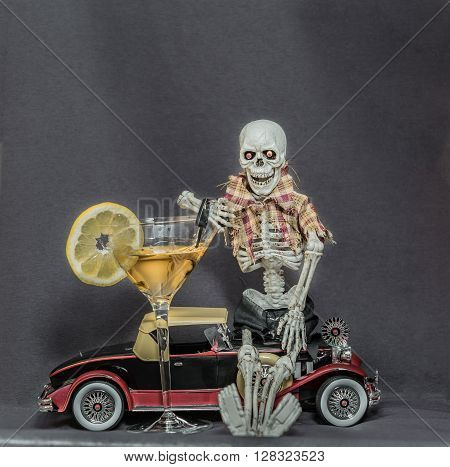 A skeleton sitting on old vintage classic car and holding glass with alcohol fluid on grey background,- message of drink and drive consequences