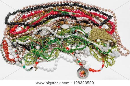Closeup view of various colorful jewelry and necklaces isolated on white background