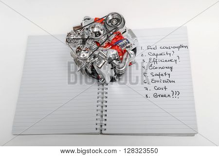 View of small model of transport truck engine, on open paper notebook with many various written words against white background