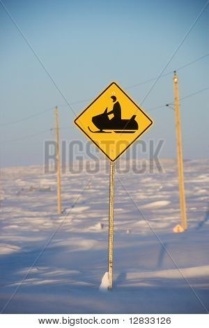 Snowy landscape with snowmobile crossing sign.