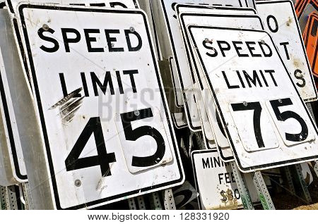 Used signs for traffic speed limits are stacked vertically in piles