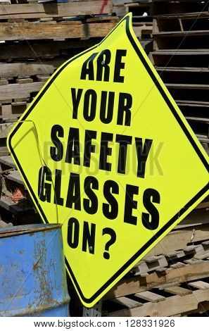 A sign in a warehouse yard indicates the requirement of wearing safety glasses.