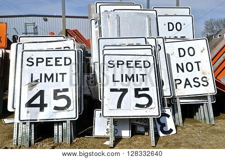 Highway road signs  posting speed limits stacked in rows at an outdoor storage area