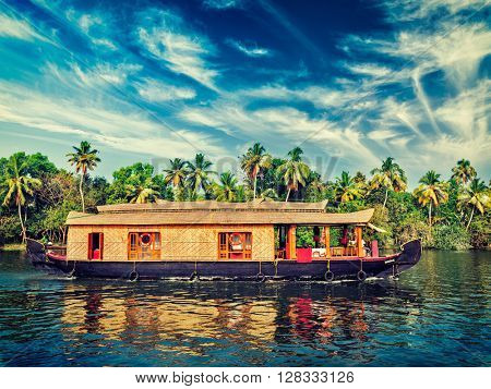 Travel tourism Kerala background - vintage retro effect filtered hipster style image of houseboat on Kerala backwaters. Kerala, India