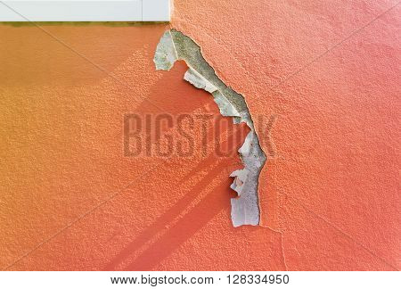 Deteriorated exterior paint of orange house wall
