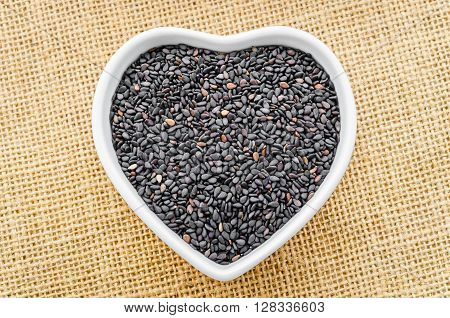 Black Sesame in white bowl on sack background.