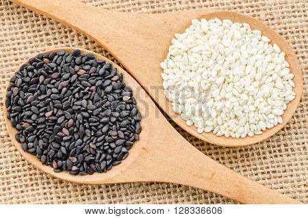 White sesame and black sesame seeds on wooden spoon.