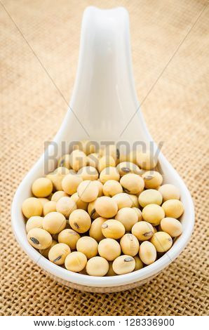 Soy beans in white spoon on sack background.