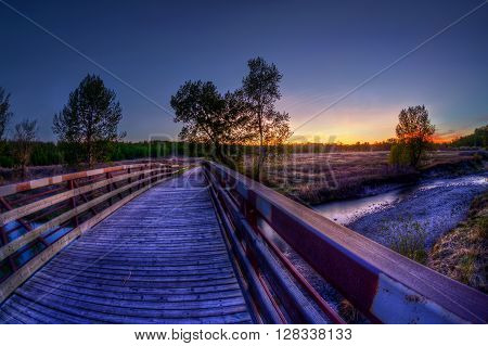 Wooden Bridge Leading To Sunset Landscape