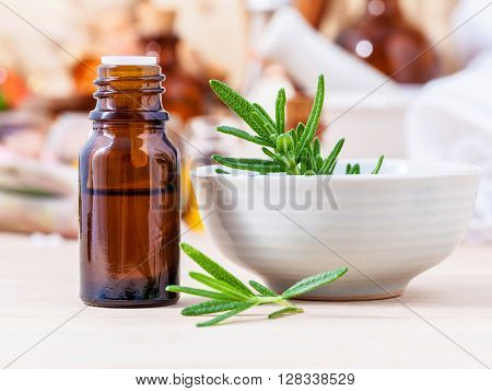 Fresh Rosemary And Essential Oil With Shallow Depth Of Field Setup On Wooden Background .