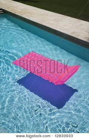 Pink lounge float in empty swimming pool.