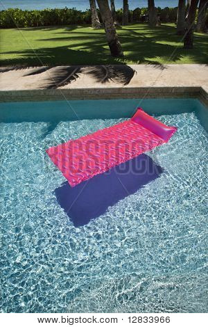 Pink float in empty swimming pool.