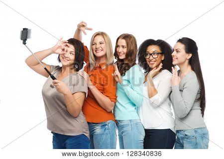 friendship, technology, body positive and people concept - group of happy different size women in casual clothes taking picture with smartphoone on selfie stick