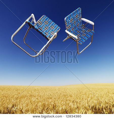 Two lawn chairs in mid-air above a field of wheat with blue sky.