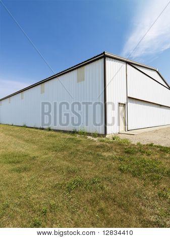Plain large aluminum building in rural setting.