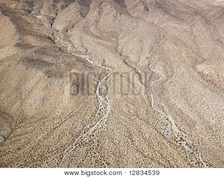 Aerial view of torrid California desert with rocky landforms.