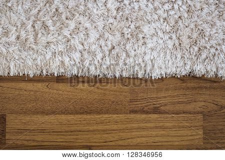 Close-up fluffy luxury carpet on laminate wood floor