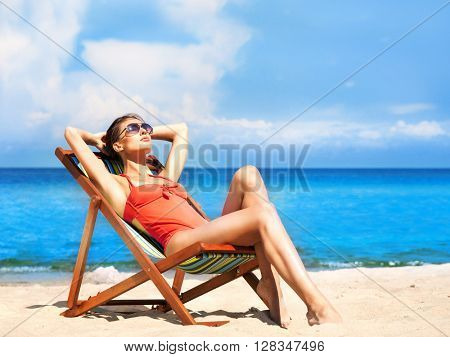 Beautiful, seductive girl in alluring swimsuit getting a suntan while lying in the sun chair on the beach.