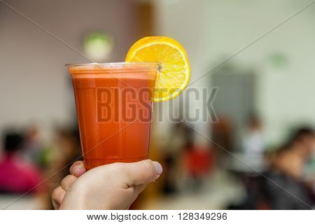 A person holding an orange and carrot smoothie in a plastic recyclable cup