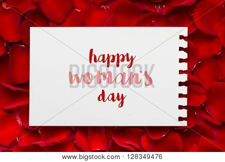Happy woman day message on empty sheet of paper and rose petals