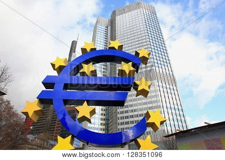 FRANKFURKT, GERMANY - DEC 17, 2011:  Euro sign at European Central Bank headquarters in Frankfurt Germany with dark dramatic clouds symbolizing a financial crisis