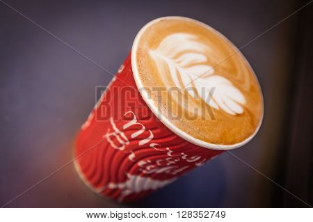 Take away cup of cappucchino on a table in a restaurant