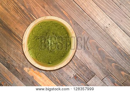 Wooden bowl of green tea powder on wood texture background stock photo
