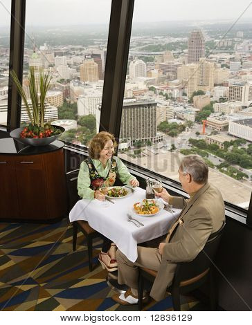 Mature couple dining in fancy restaurant by window with rooftop view of urban landscape.