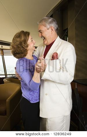 Mature Caucasian couple dancing and laughing.