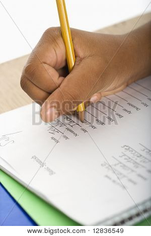 Hand of African American girl at school desk writing in notebook with pencil.